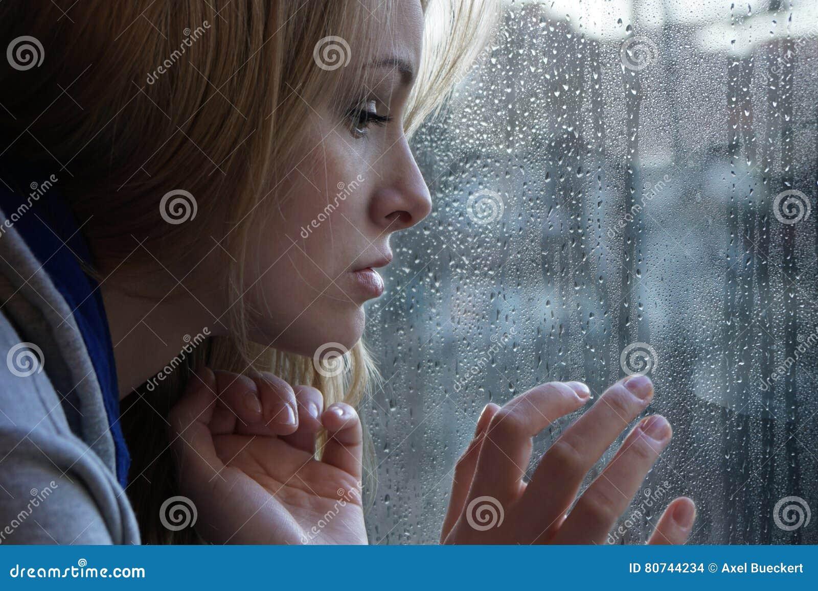 Ledsen ung kvinna som ser till och med fönster på regnig dag