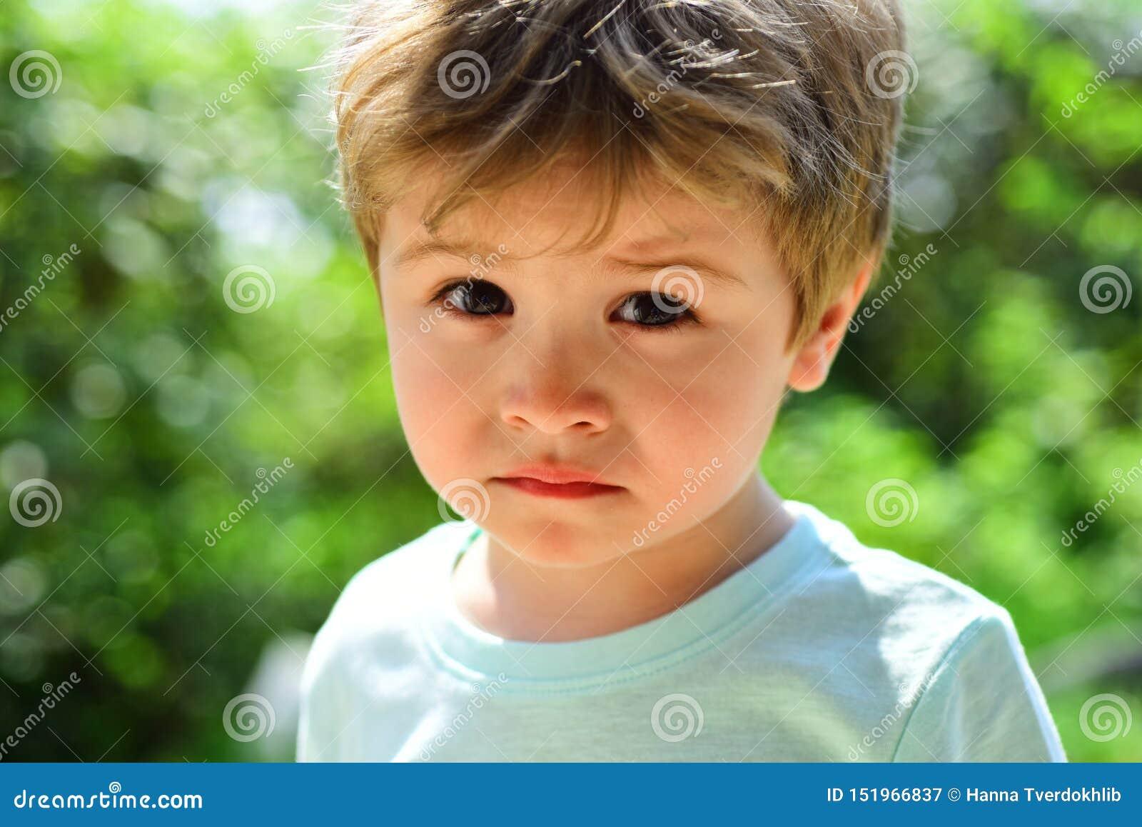 Ledset barn, närbildstående Ett frustrerat barn utan lynne Ledsna sinnesrörelser på en härlig framsida Barn i natur