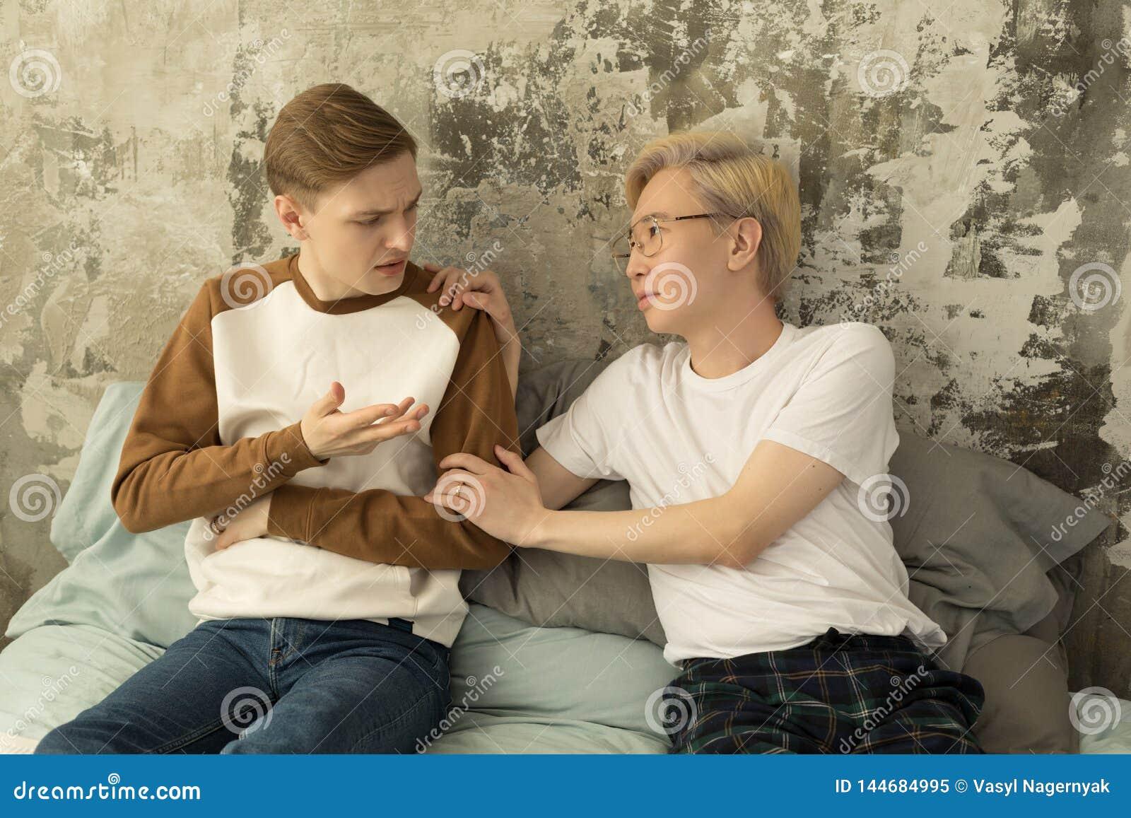Ledset eftertänksamt ungt glat manligt tänka av förhållandeproblem som sitter på säng med den kränkta pojkvännen