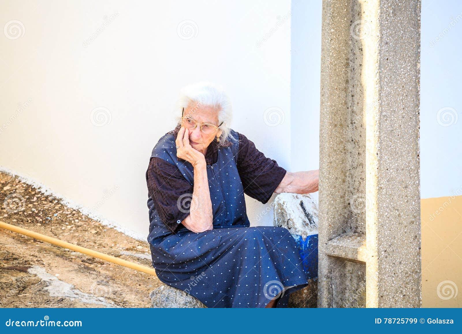 Ledset och att tänka, worring sitta för äldre kvinna som är utomhus-