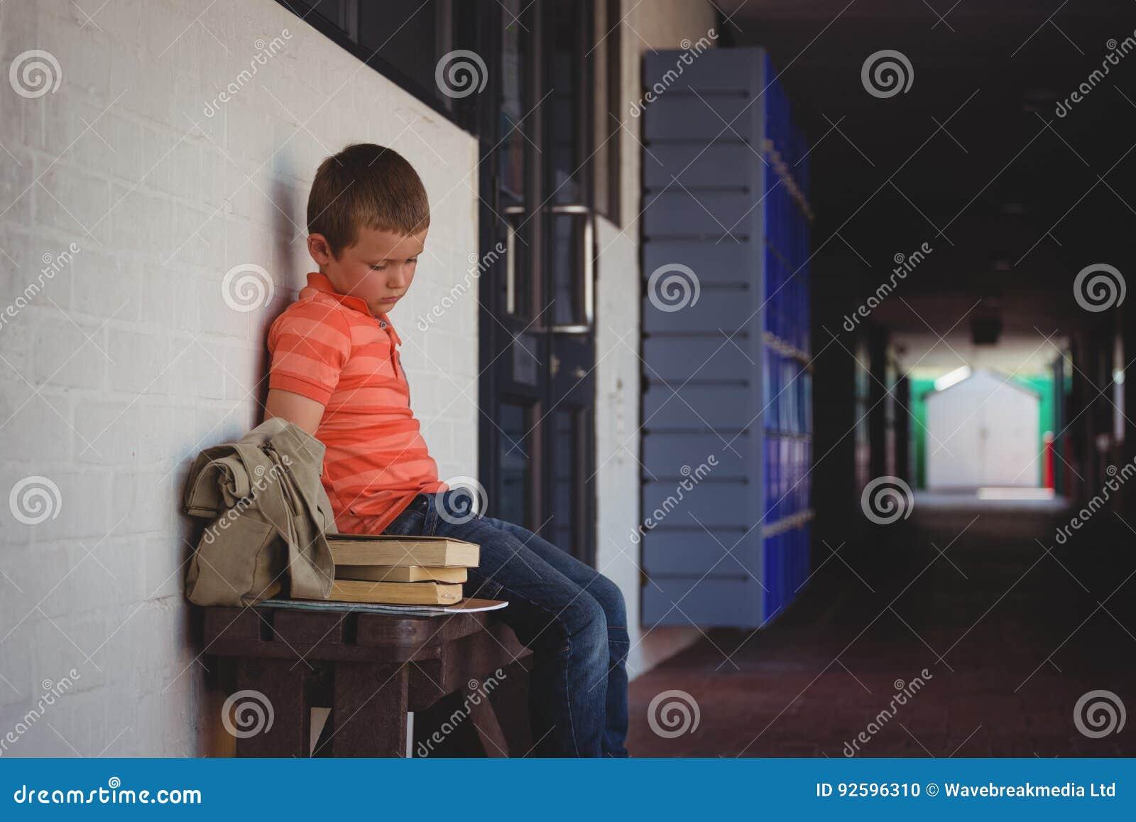Ledset pojkesammanträde på bänk vid väggen i korridor