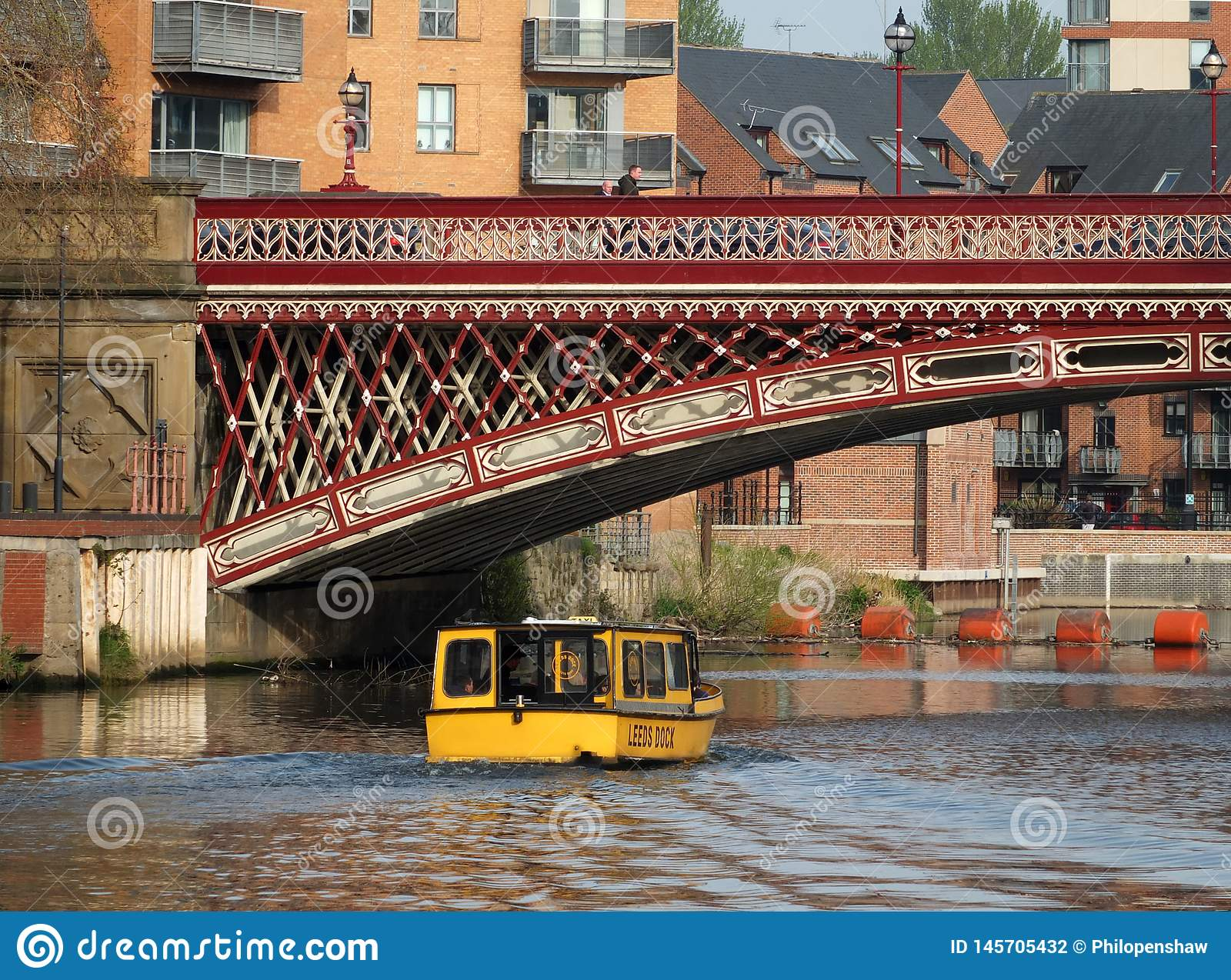 a yellow water taxi boat passing under crown point bridge over the river aire in leeds
