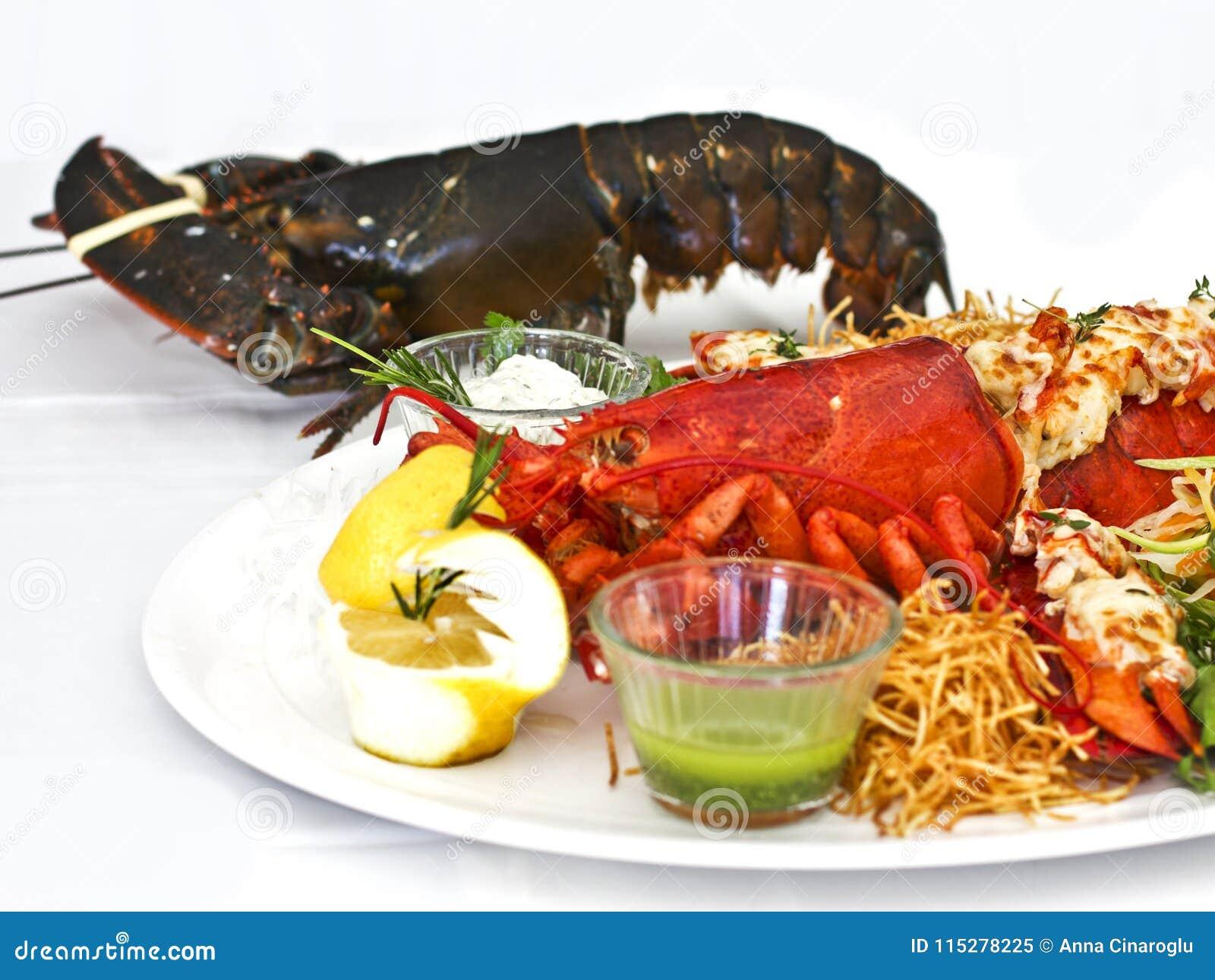 Leef en kookte zeekreeft met groenten op een witte plaat Isolat