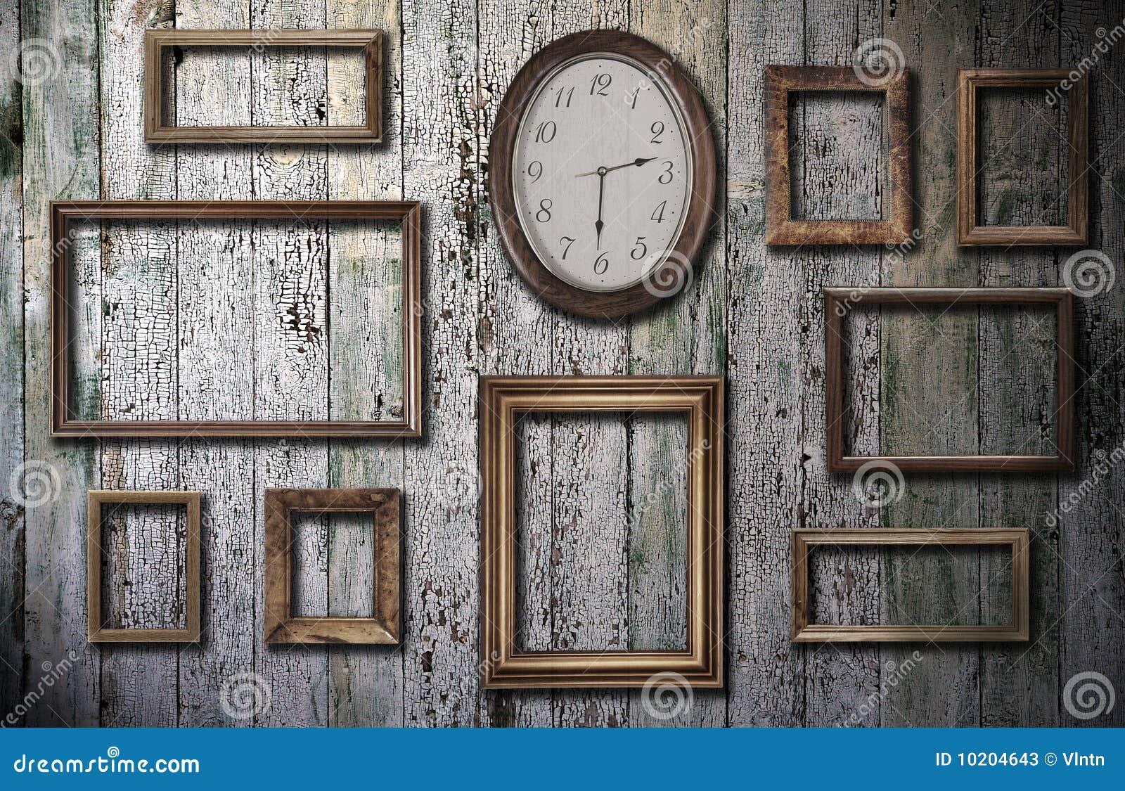 Leeg frames en horloge op houten muur