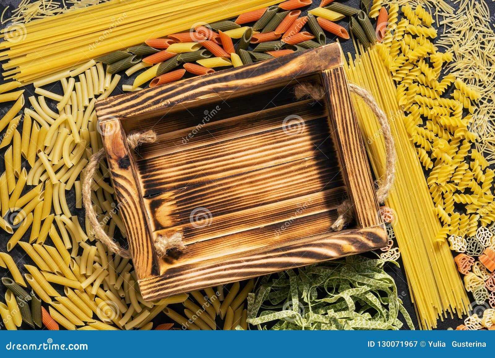 Leeg houten dienblad en kader van ruwe gevarieerde deegwaren De hoogste vlakke mening, legt Het concept deegwaren