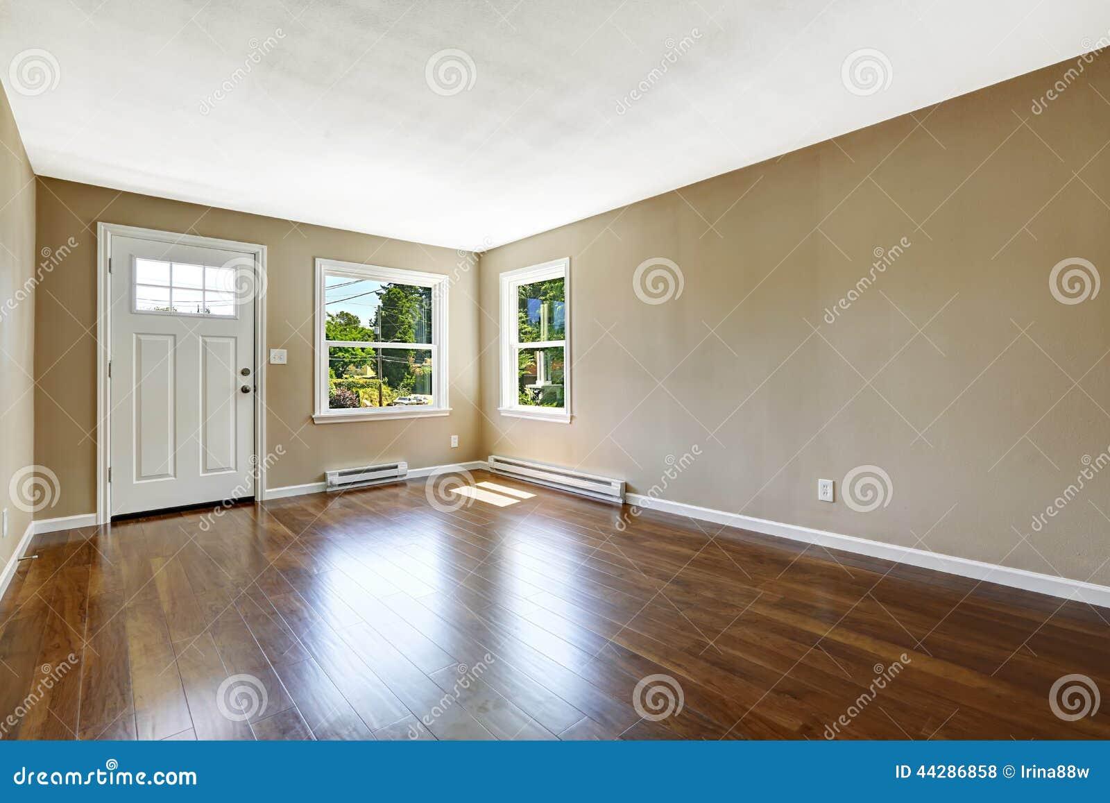 Leeg huisbinnenland hardhoutvloer en beige muren stock foto