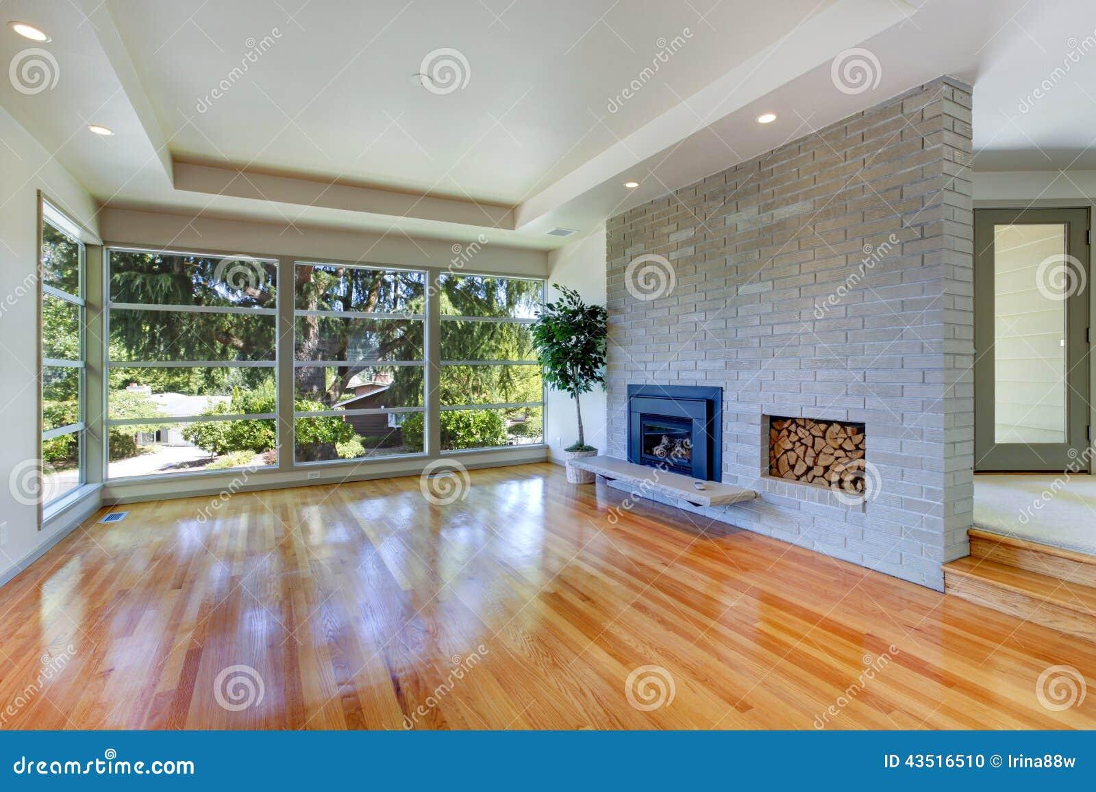 Leeg huisbinnenland woonkamer met glasmuur en bakstenen muur stock