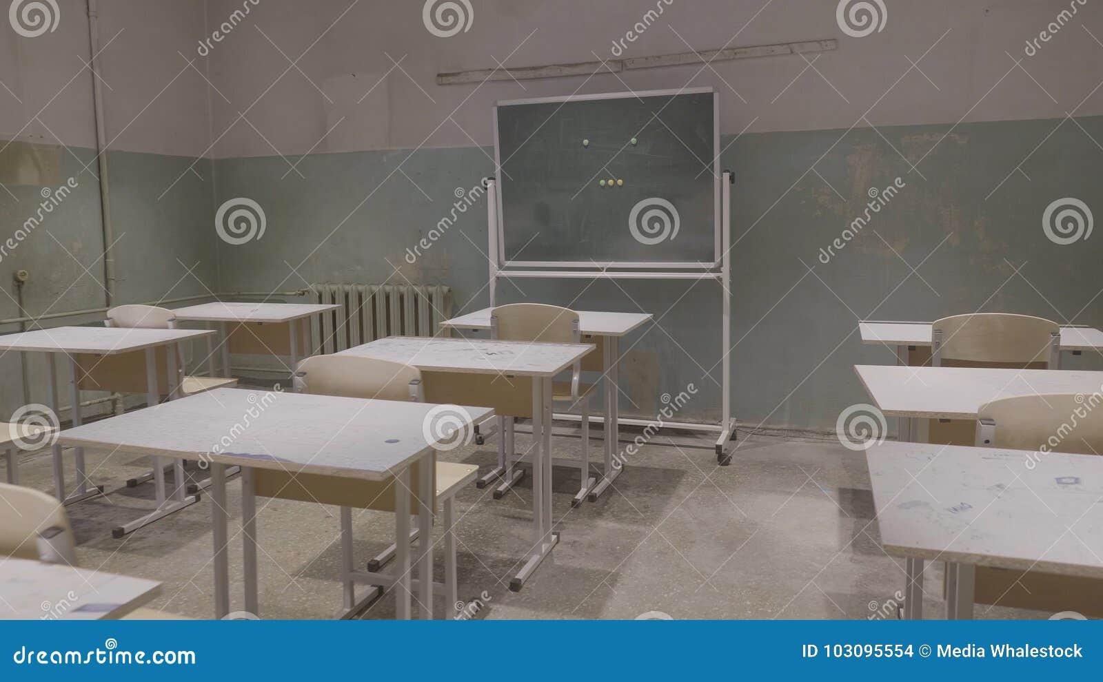 Leeg klaslokaal met houten bureaus, witte en groene schoolborden in school Leeg Klaslokaal Verlaten Schoolklaslokaal