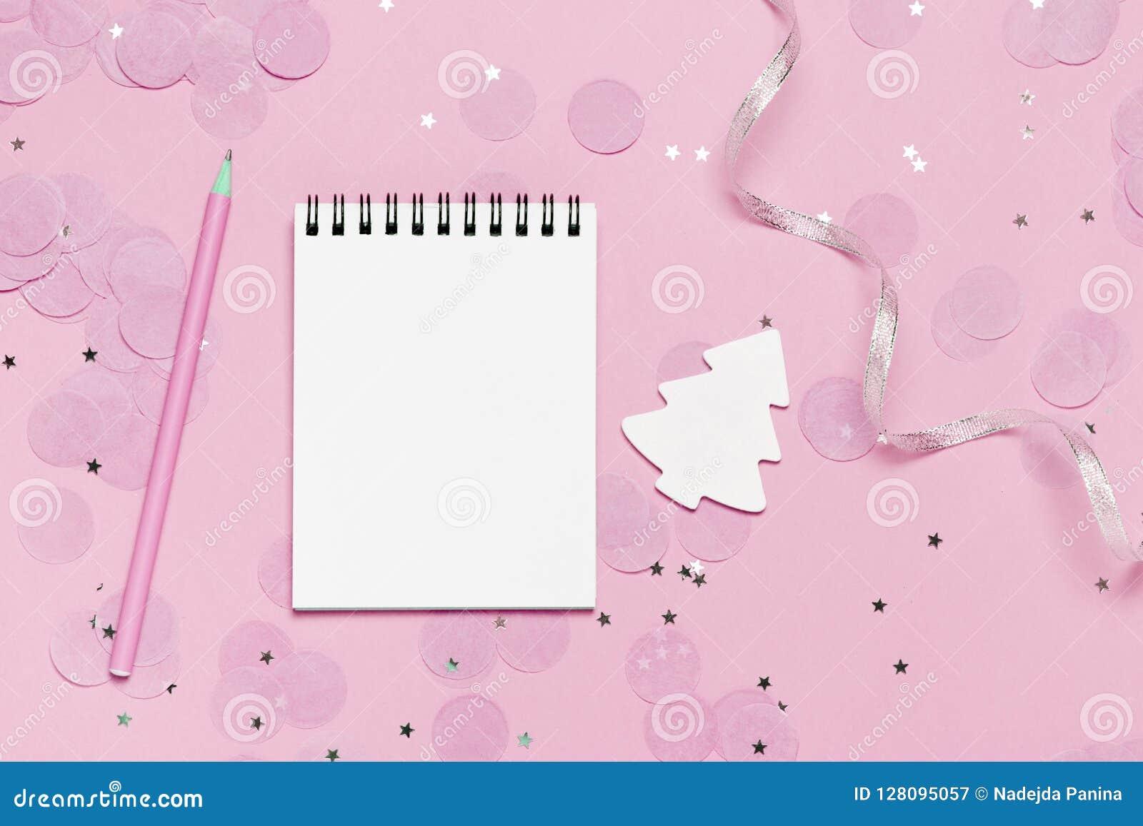 Leeg notaboek - Kerstmis en nieuwe jaarspot op malplaatje met roze confettien op roze achtergrond