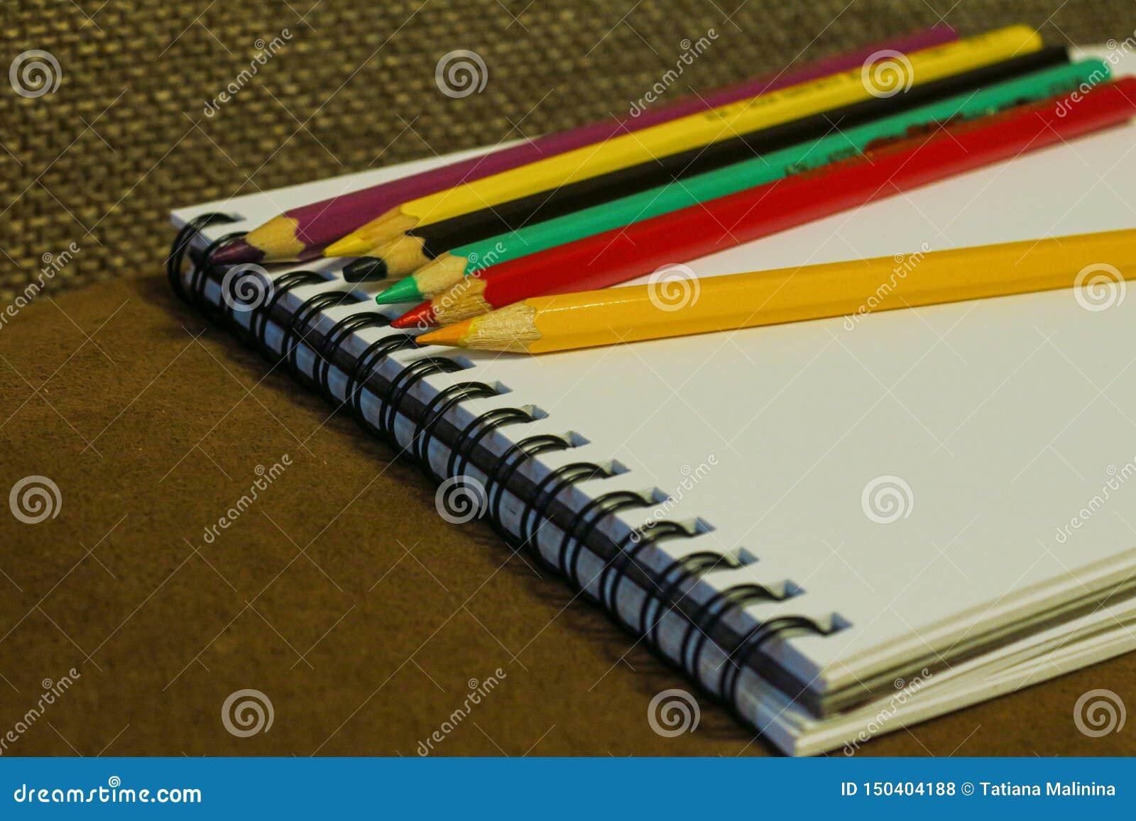 Leeg notitieboekje en kleurrijke potloden op bruine achtergrond,