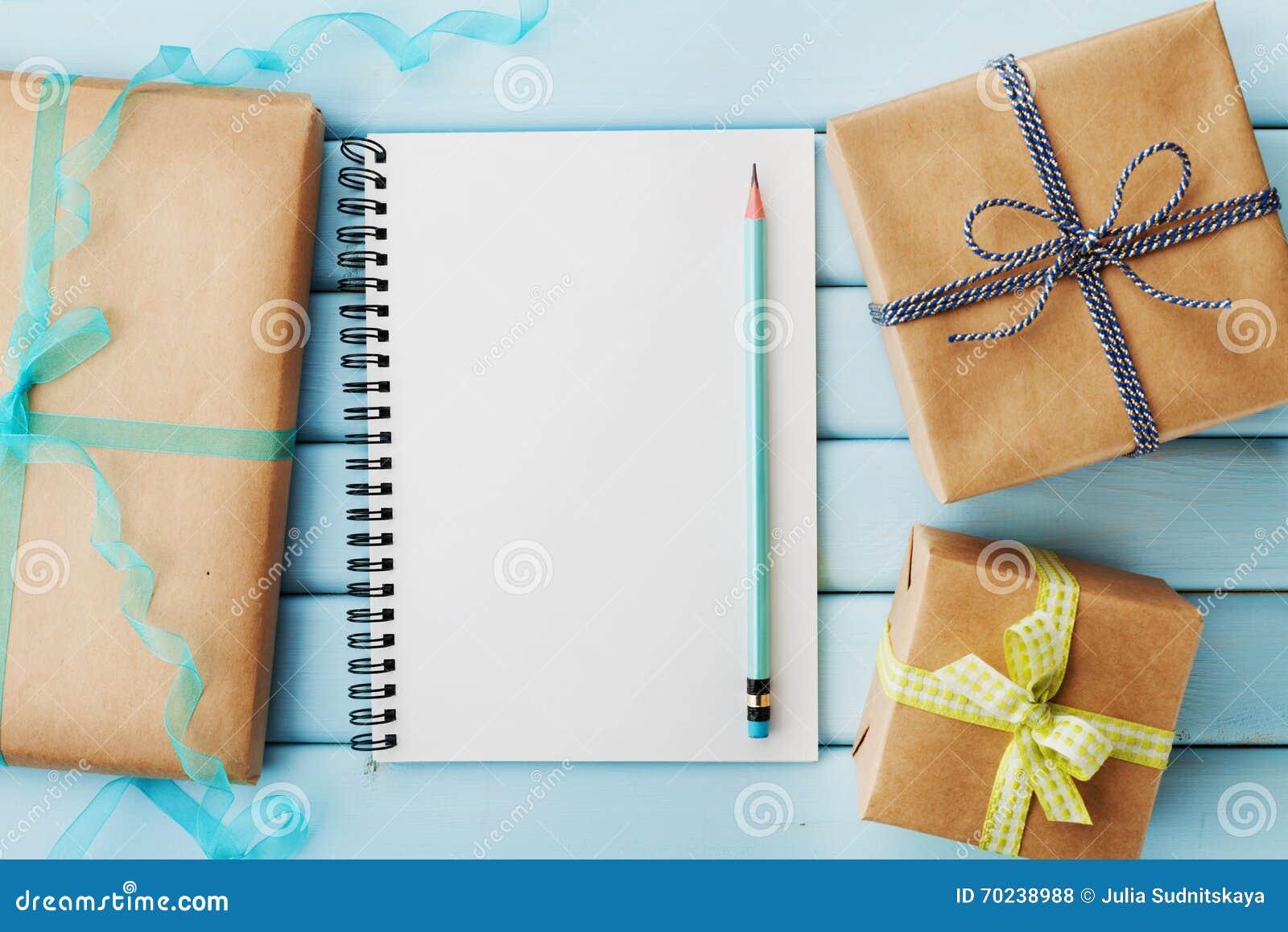 Leeg notitieboekje, potlood en gift of huidig die vakje in kraftpapier-document op blauwe houten lijst wordt ingepakt