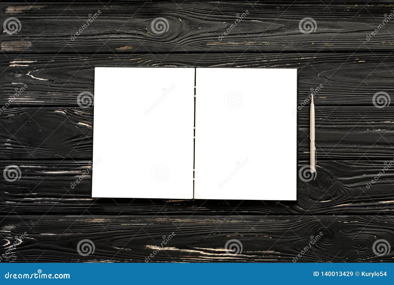 Leeg open notitieboekje en zilveren pen op de zwarte houten achtergrond