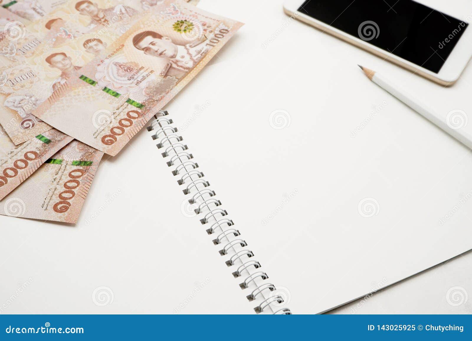 Leeg wit spiraalvormig notitieboekje met wit potlood, mobiele telefoon en stapel van nieuwe 1000 Thaise Bahtbankbiljetten