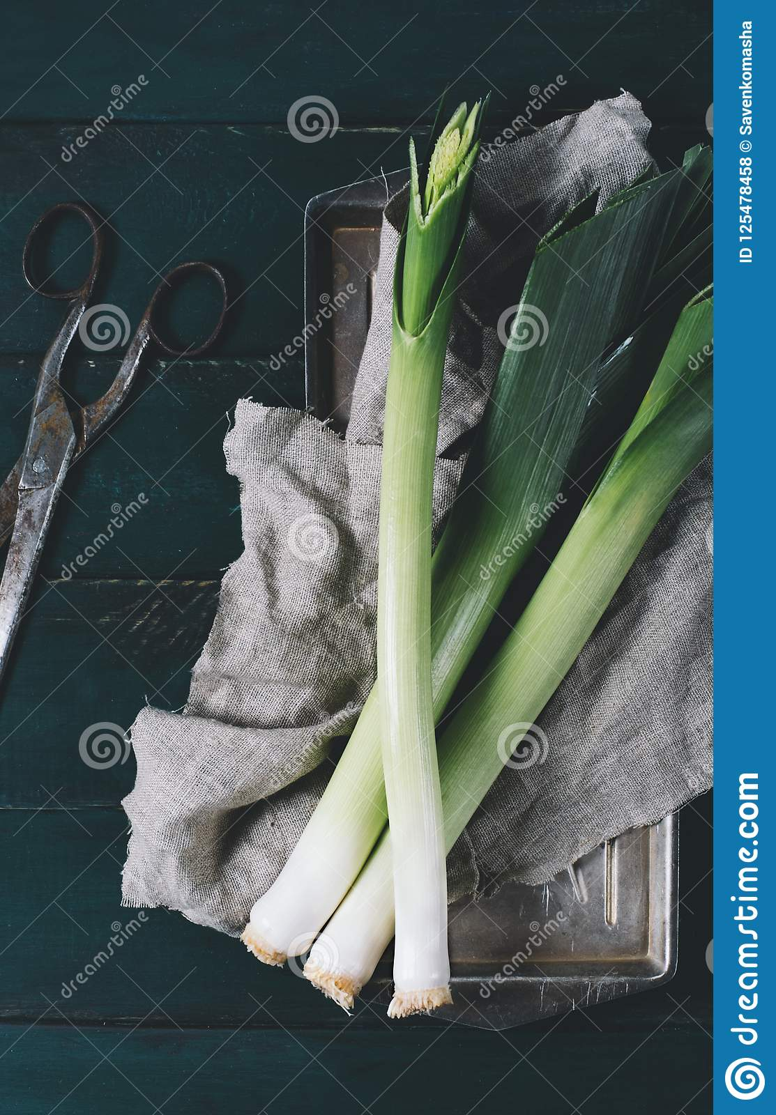 Leek and scissors on a light textile and metal plate on a dark background of the aged wooden boards vintage vertical top view