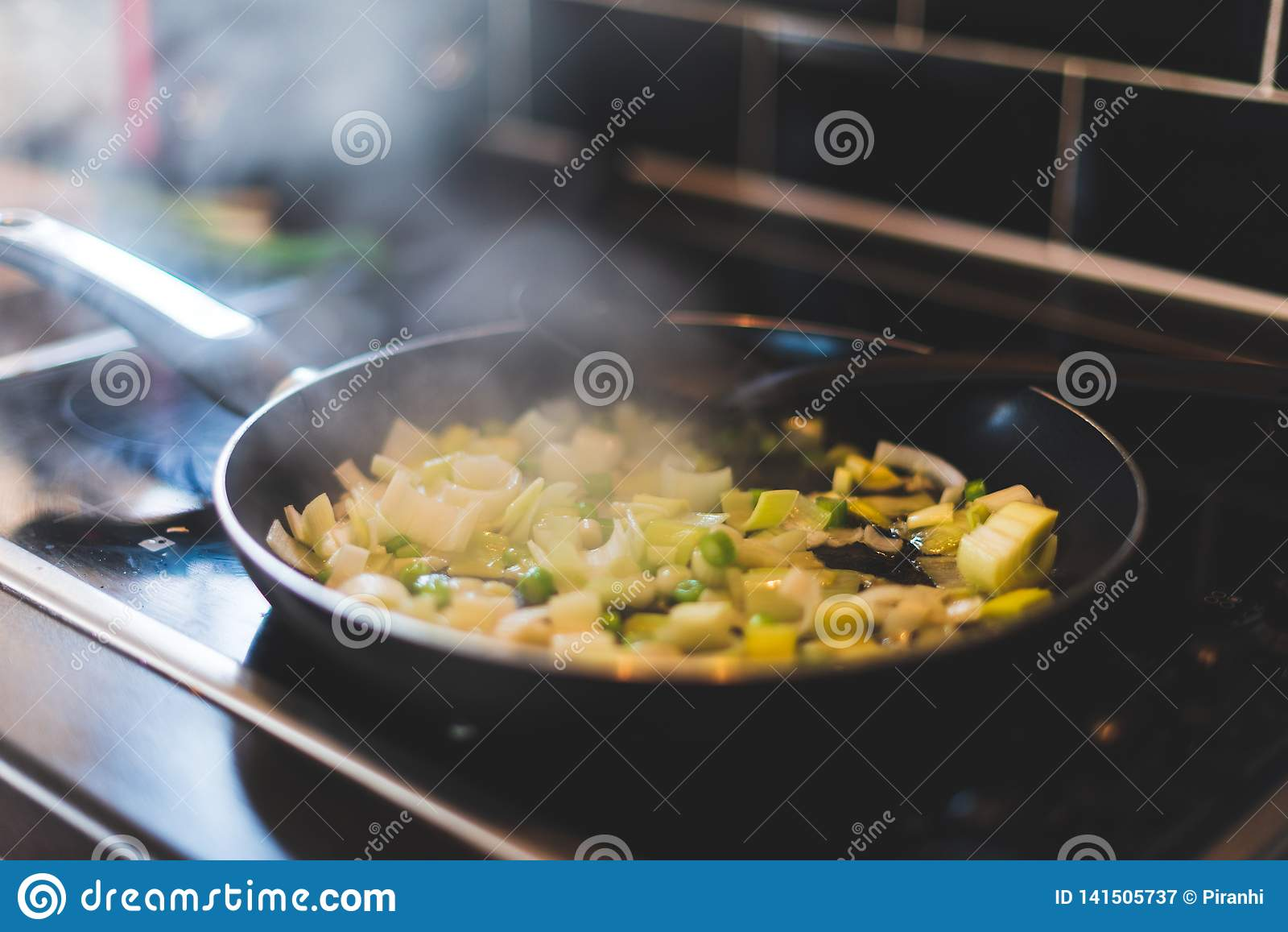Leeks and other vegetables are being cooked in a frying pan