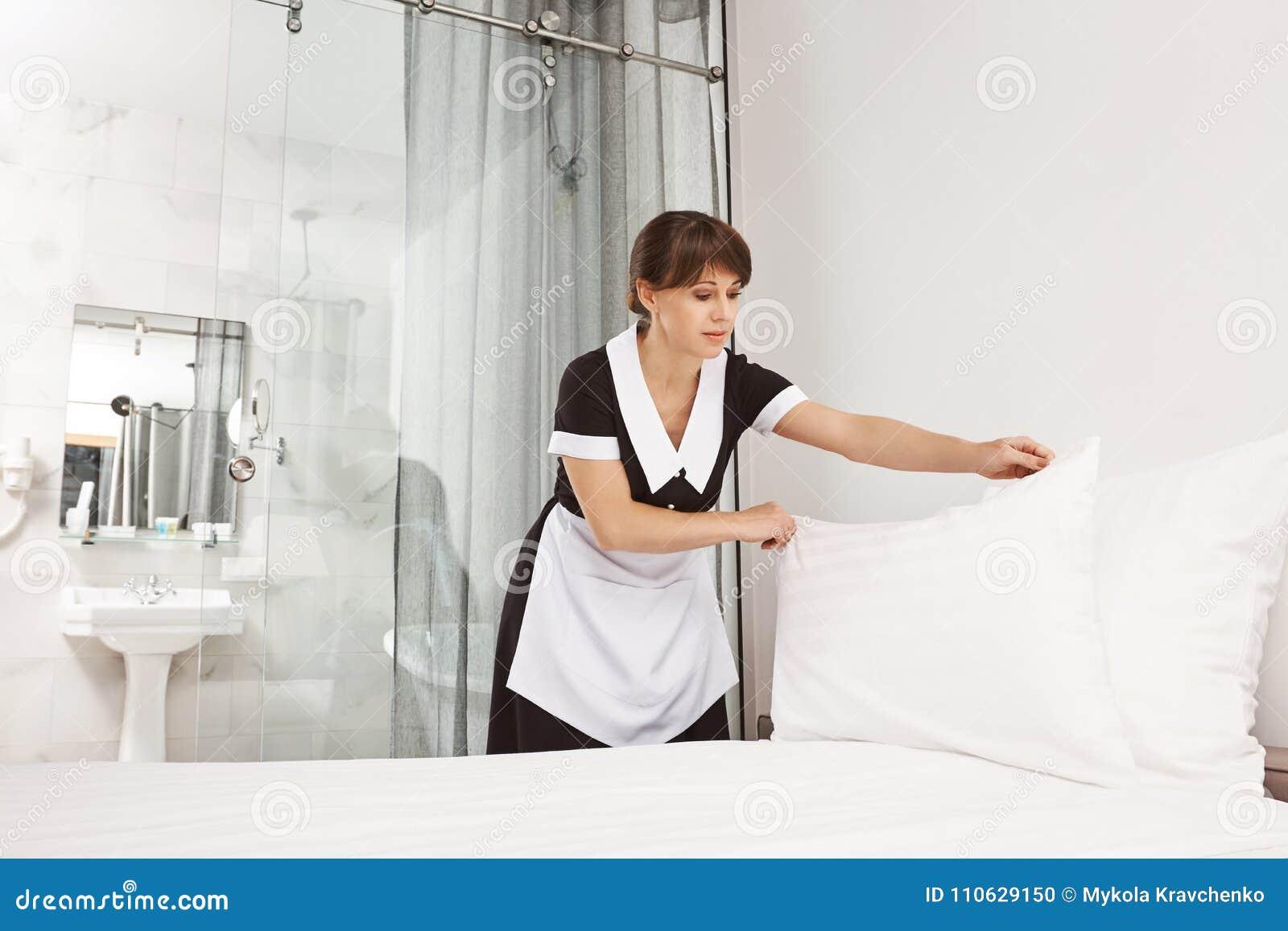Leendet av klienten gör mig att känna mig bättre Kvinnlig i enhetlig danandesäng för hembiträde i sovrummet som sätter kudden eft