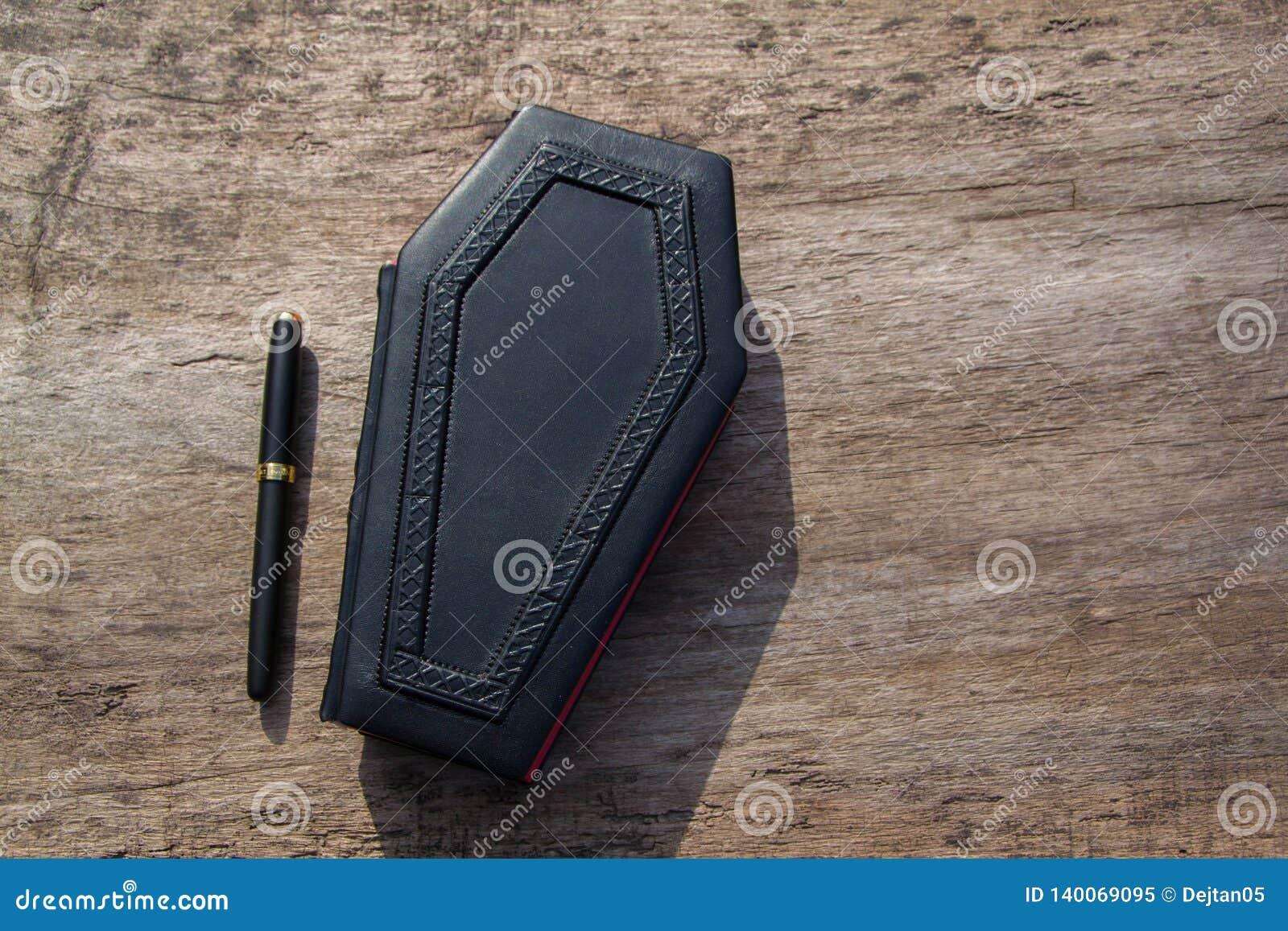 Leerboek in vorm van doodskist, met een potlood op het