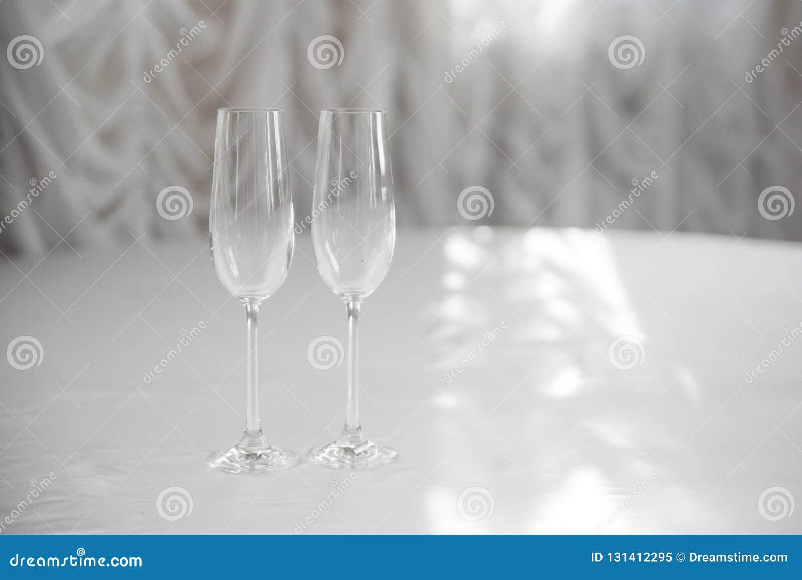 Leere Champagnergläser auf einer weißen Tischdecke vor dem hintergrund der weißen Vorhänge in der Hintergrundbeleuchtung