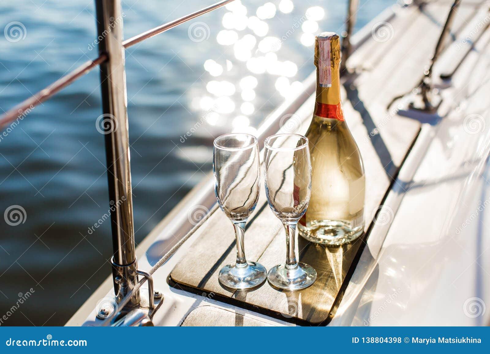 Leere Gläser und Flasche mit Champagner mit Seehintergrund
