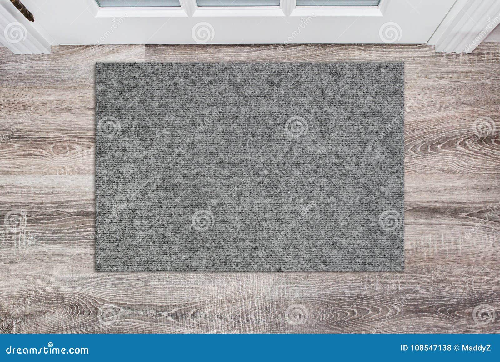 Leere graue woolen Fußmatte vor der weißen Tür in der Halle Matte auf Bretterboden, Produkt Modell