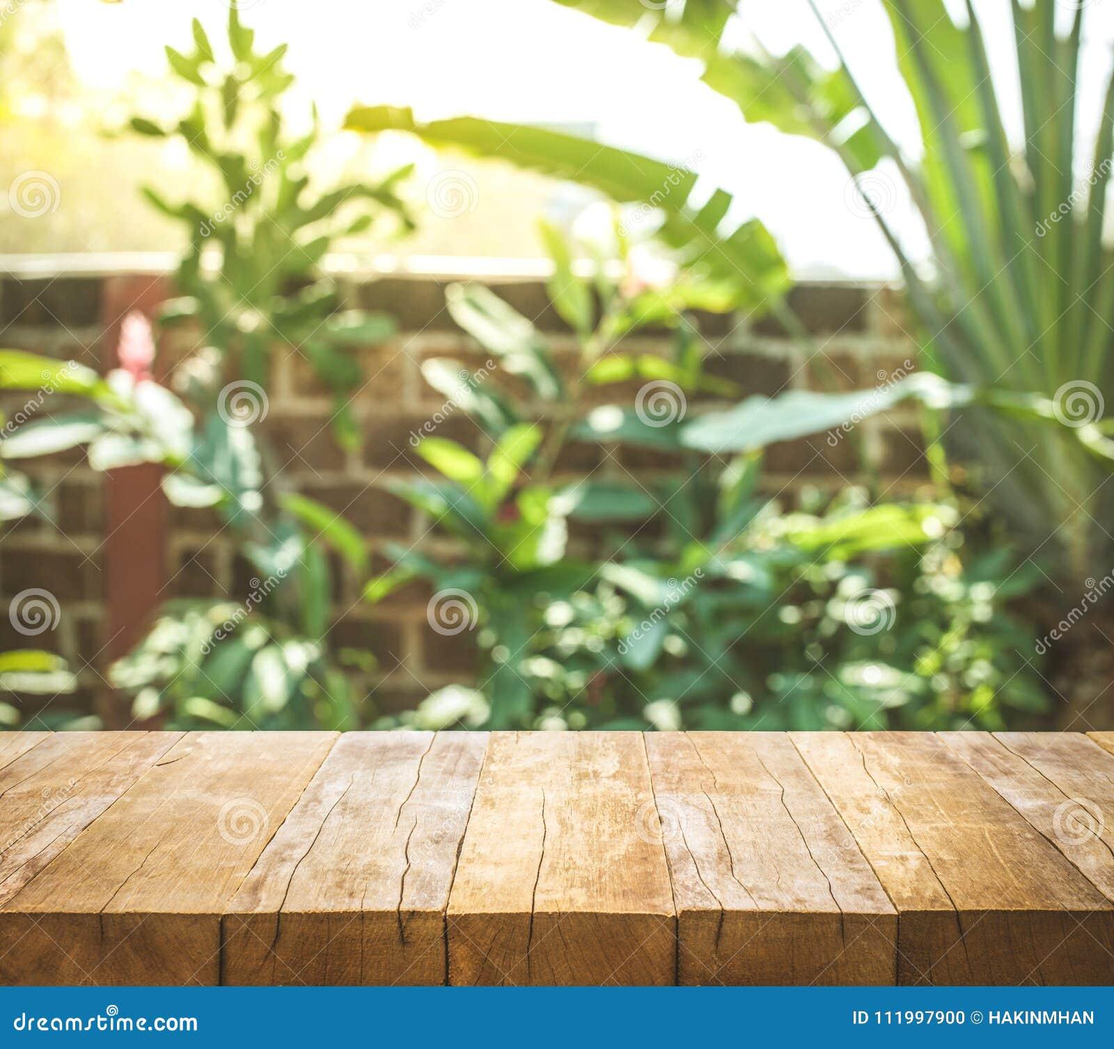 Leere hölzerne Tischplatte auf Unschärfezusammenfassungsgarten- und -haushintergrund