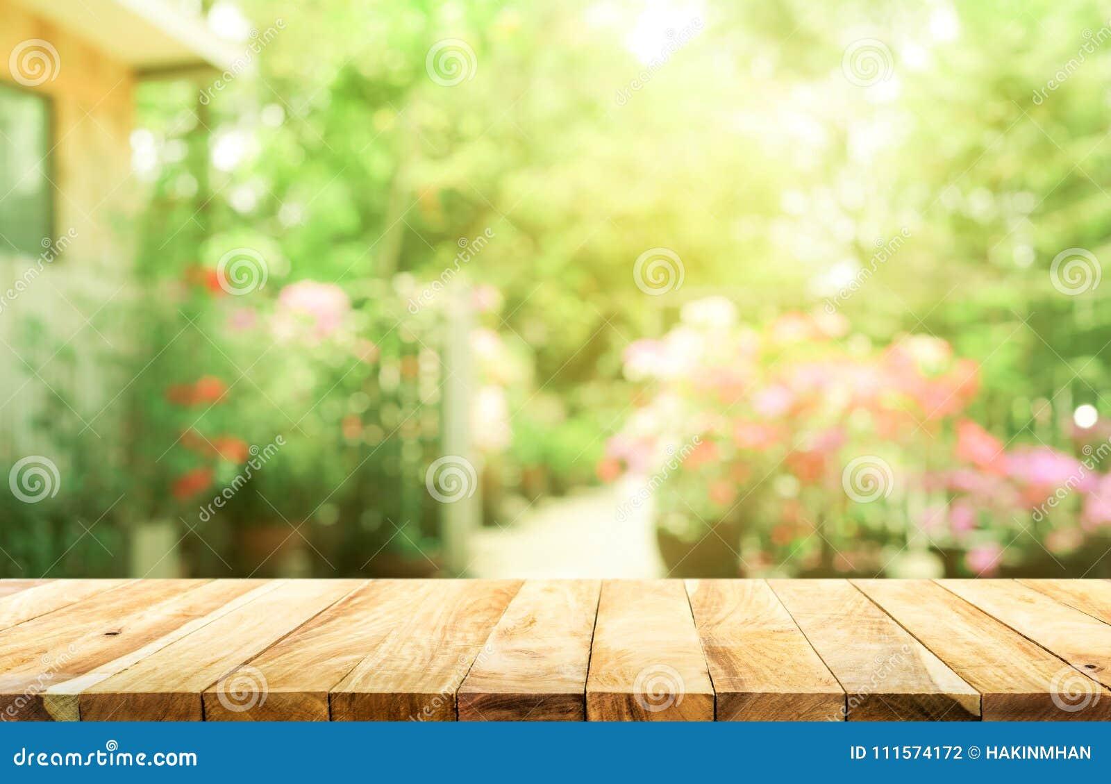 Leere hölzerne Tischplatte auf Unschärfezusammenfassungsgrün vom Garten