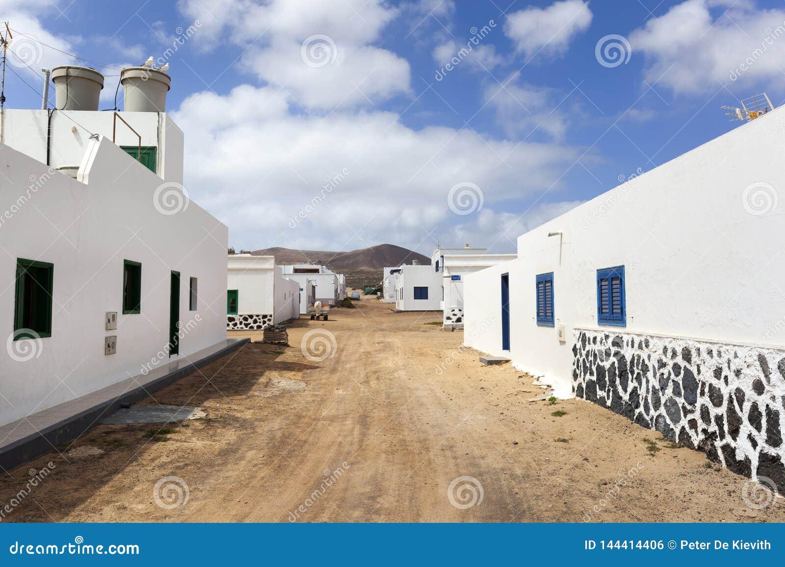 Leere Stra?e mit Sand und wei?e H?user in Caleta de Sebo auf dem Insel La Graciosa