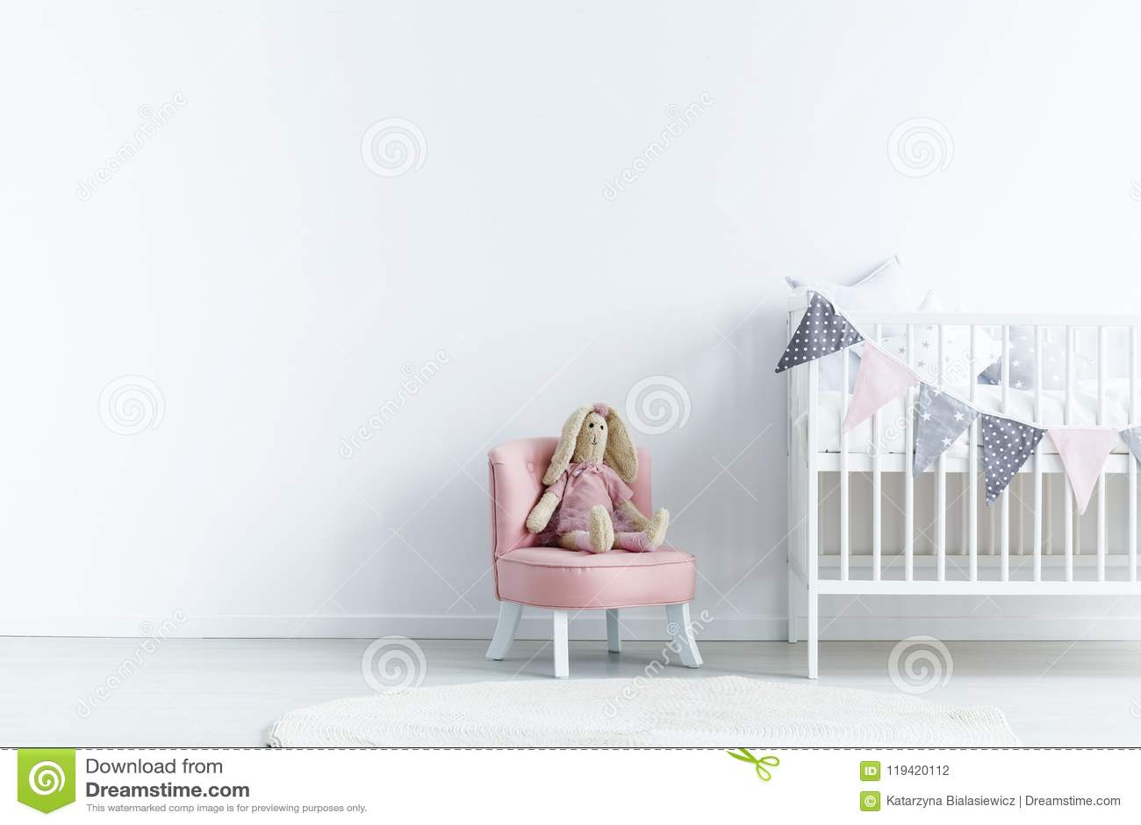 Leere Wand als Nächstes a zum Stuhl mit einem Kaninchen und einer Krippe mit Dreiecken