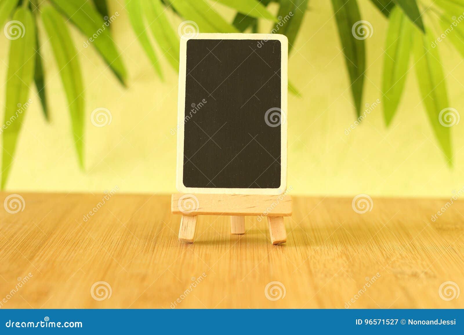 Leeren Sie Schiefer in der Höhe, um eine Mitteilung zu schreiben, die auf einem Gestell alles auf Bretterboden und grünem Laubhin
