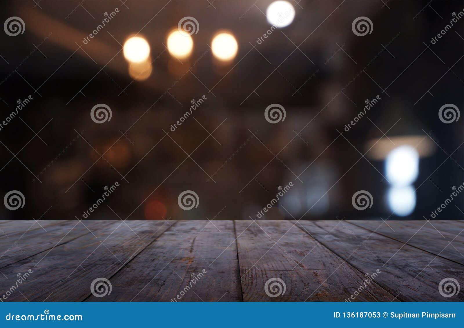 Leerer dunkler Holztisch vor Zusammenfassung verwischte Hintergrund des Café- und Kaffeestubeinnenraums Kann für Anzeige verwende