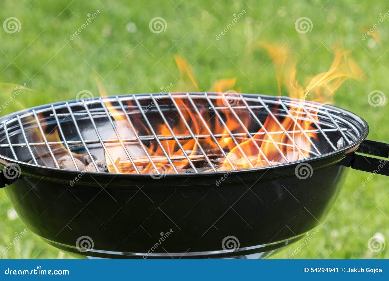 leerer grill mit feuer auf garten stockbild - bild von gras