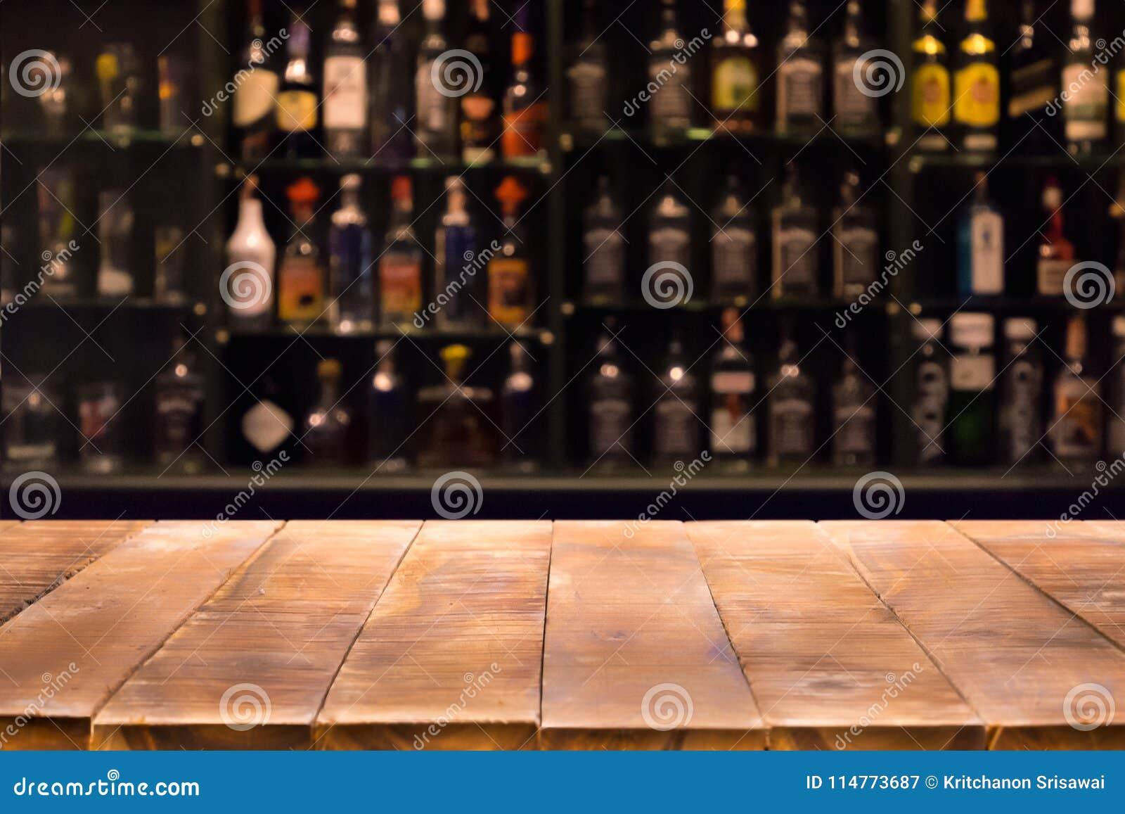 Leerer hölzerner Barzähler mit defocused Hintergrund und Flaschen des Restaurants