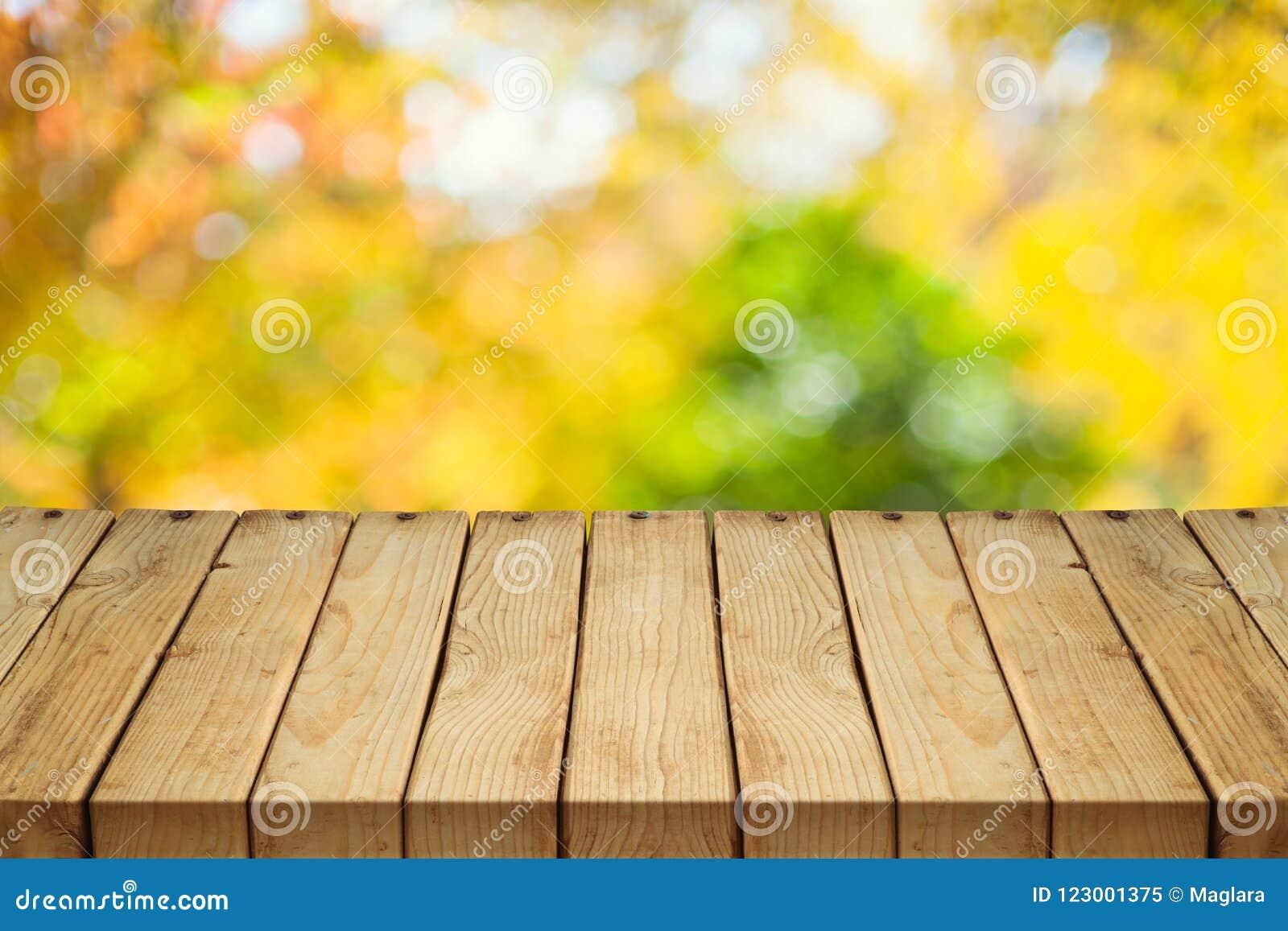 Leerer Holztisch über Herbstnatur bokeh
