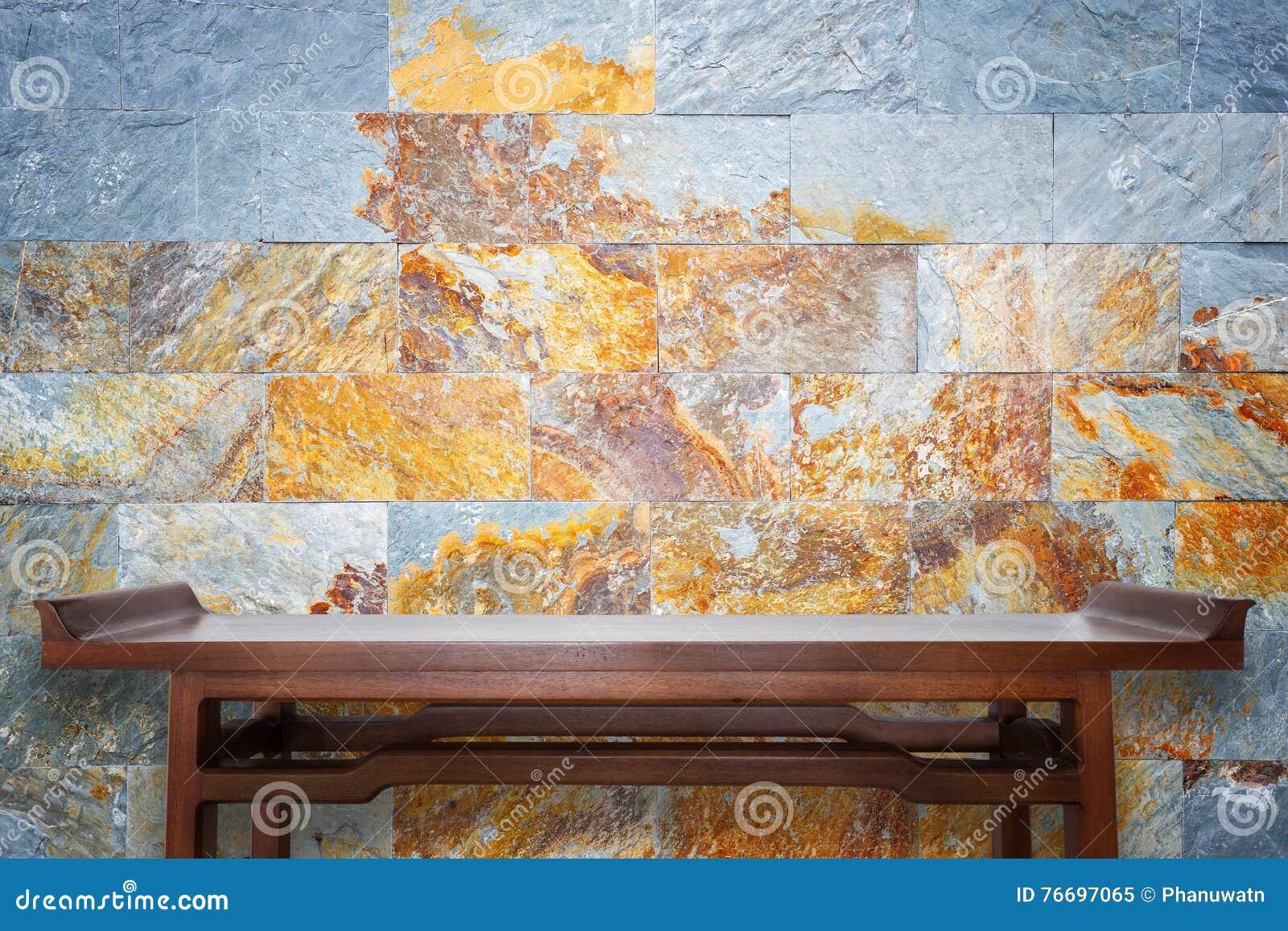 Leerer Spitzenholztisch- und Natursteinwandhintergrund
