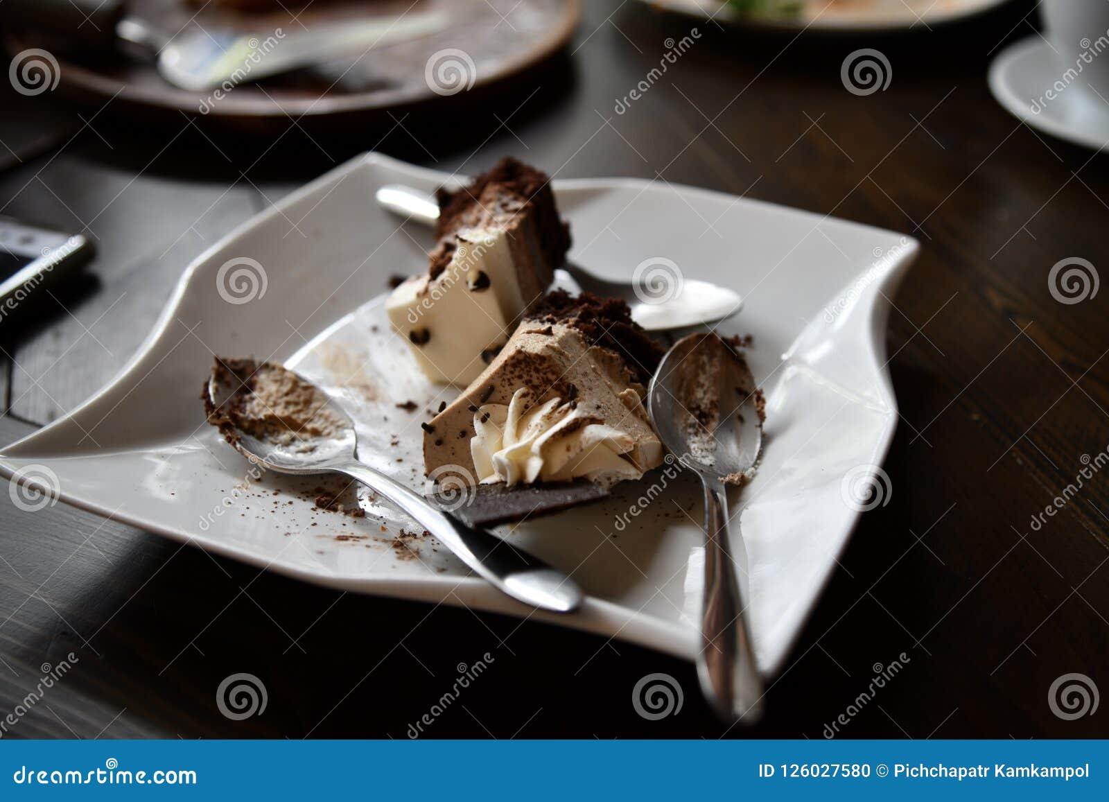 Leftover do bolo de chocolate na placa cerâmica branca