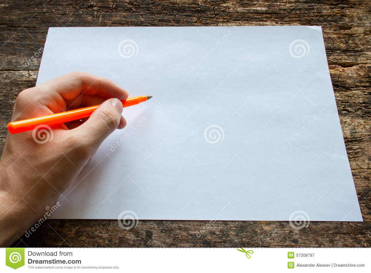 Lefty writes with a ballpoint pen on a sheet of paper on wooden table