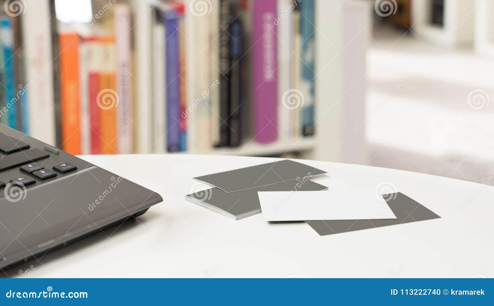 Lege adreskaartjes en laptop voor een vaag boekenrek