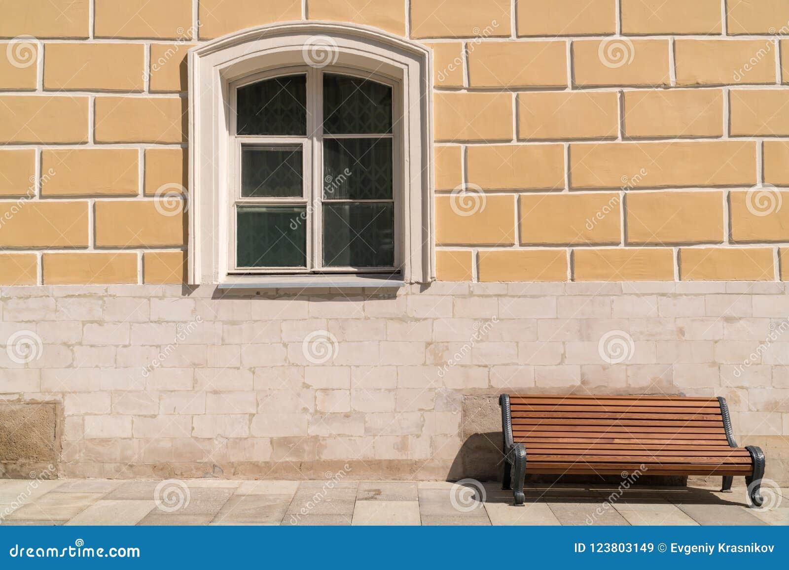 Lege bank tegen de muur met een venster