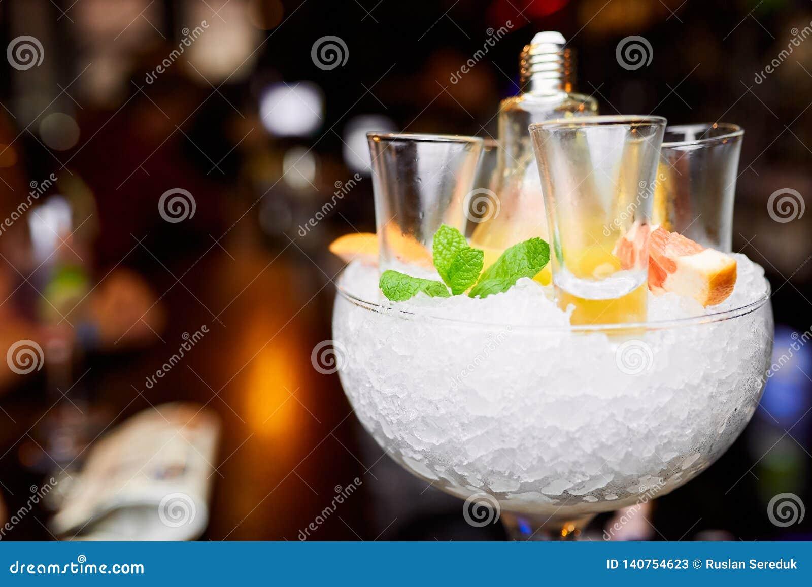 Lege schoten in een glas met ijs dat met munt en grapefruit wordt verfraaid