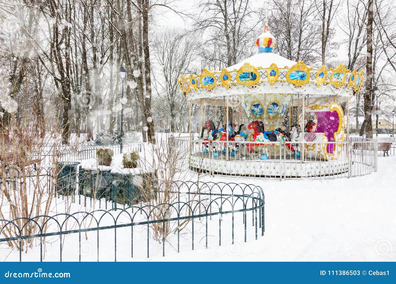 Lege uitstekende carrousel in het park op sneeuw de winterdag