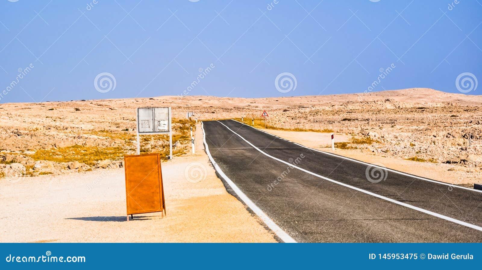Lege weg door de woestijn Houten leeg teken op de linkerkant van de foto