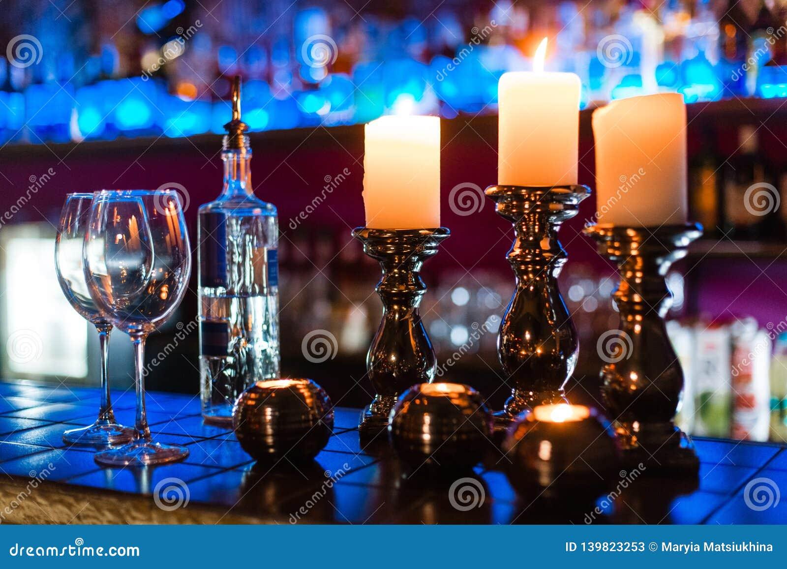Lege wijnglazen en kaarsen met de achtergrond van verlichtingslichten