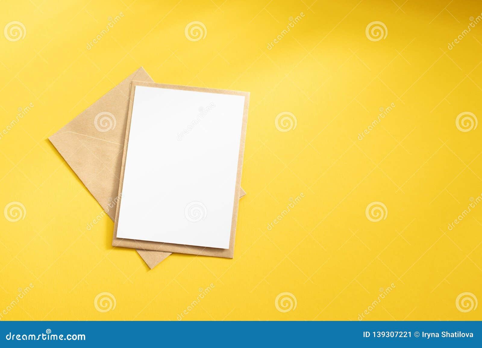 Lege witte kaart met van de het pakpapierenvelop van kraftpapier het malplaatje omhoog spot