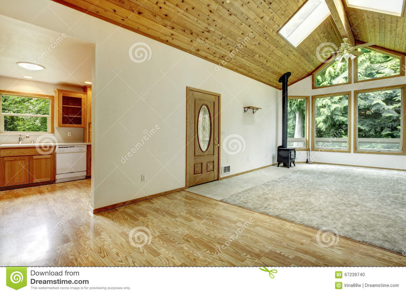 Lege woonkamer met verbonden keuken, gewelfd houten plafond, en ...