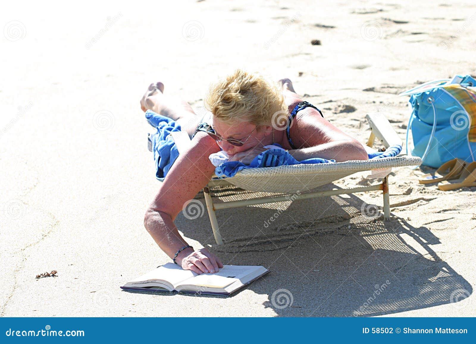 Leggendo un giorno caldo della spiaggia