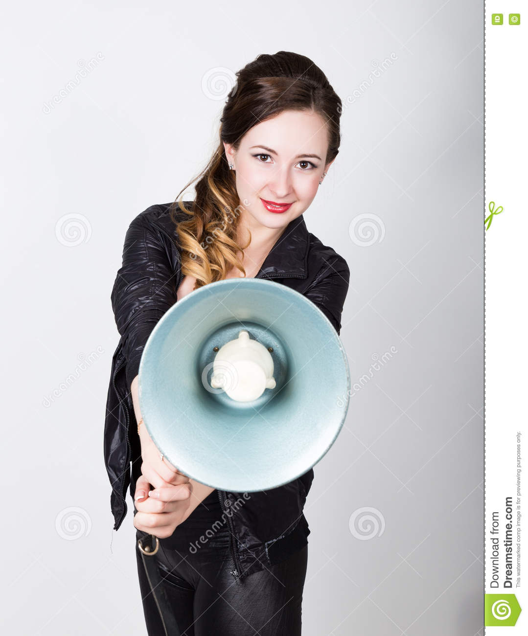 Leggy beautiful girl in black skin-tight trousers and jacket, she yells into a bullhorn. Public Relations
