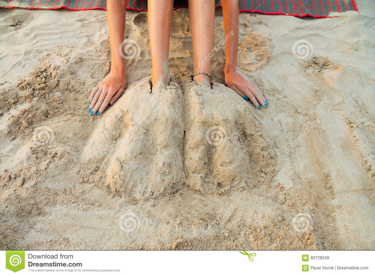 Legs beautiful young woman buried in sand on beach. woman sitting on sand