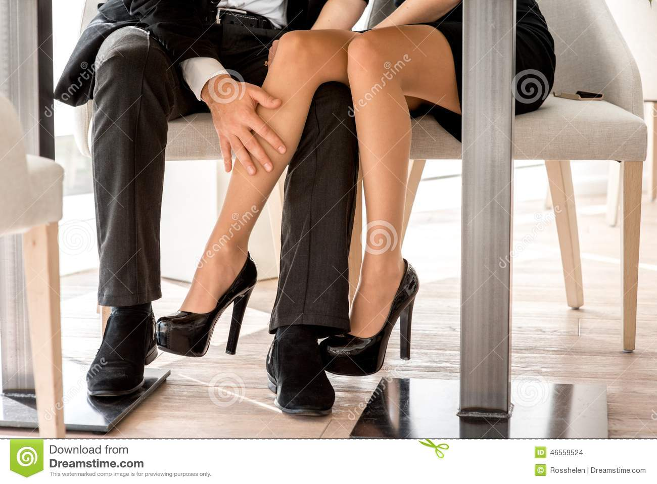 Legs Under Table : Young couple flirting with legs at the restaurant under the table.