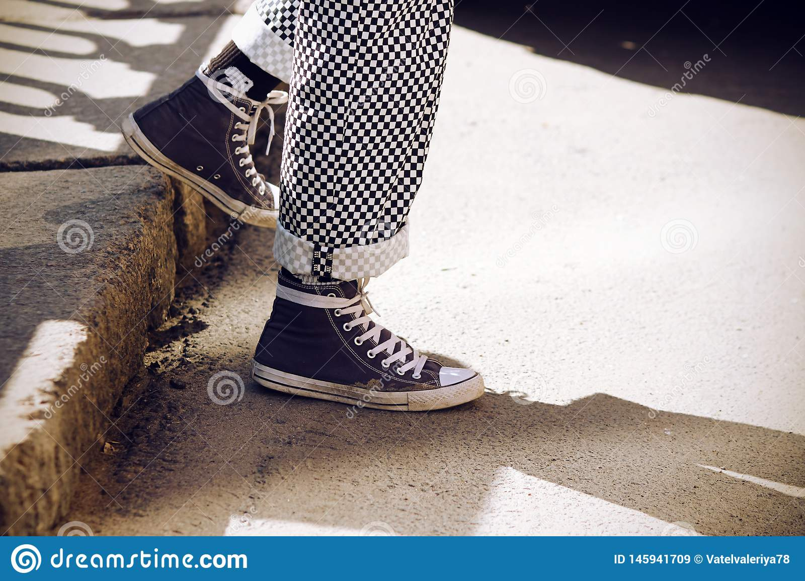 Legs dressed in plaid pants and in blue sneakers descend from the step