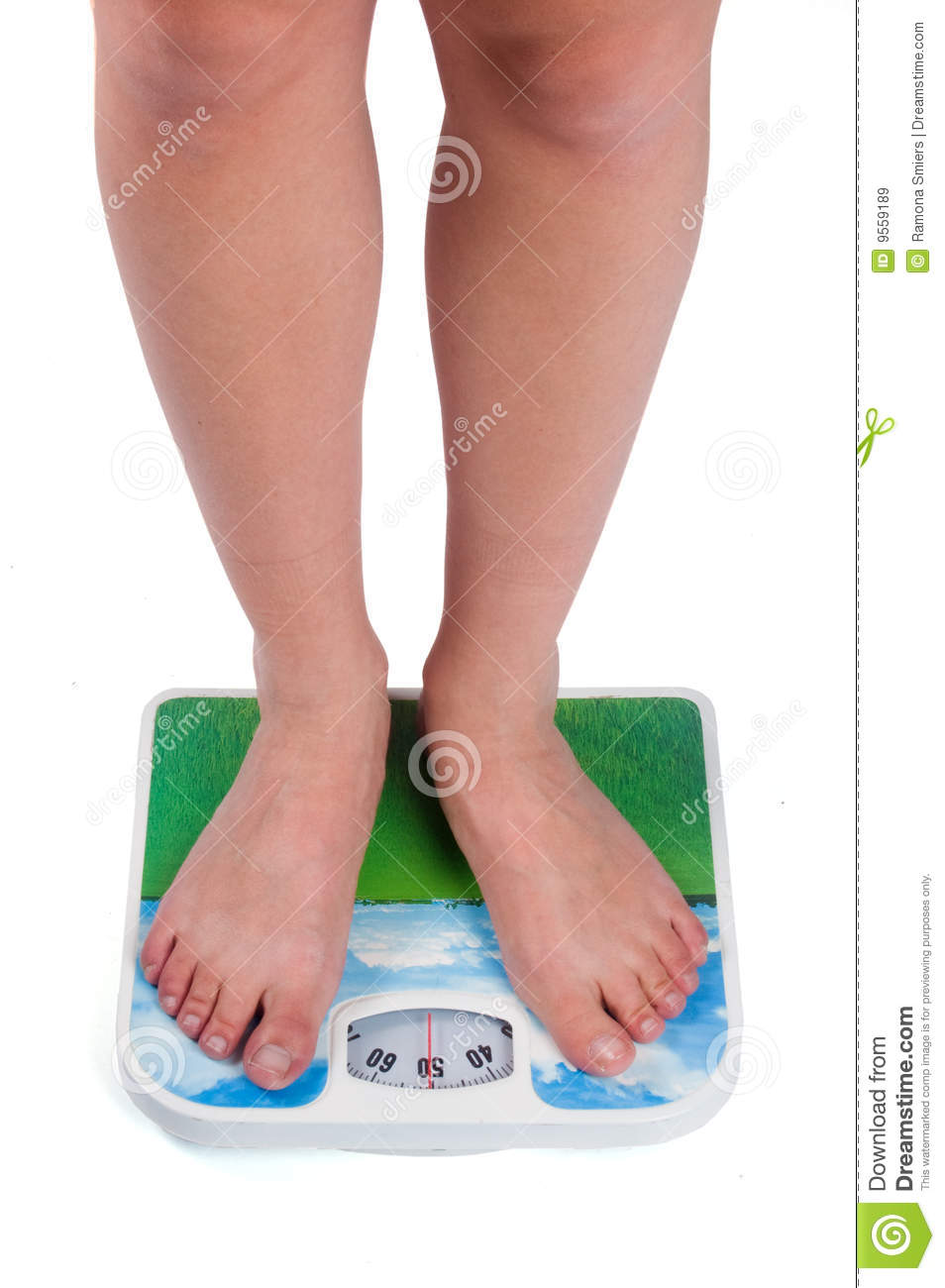 Legs Of Female Standing On Bathroom Scales Stock Image